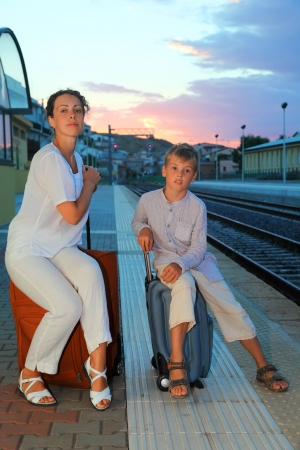 mother and little son sitting on bags on platform of railway at evening photo