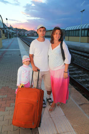 mother, father and little daughter with bag on platform of railway at evening photo
