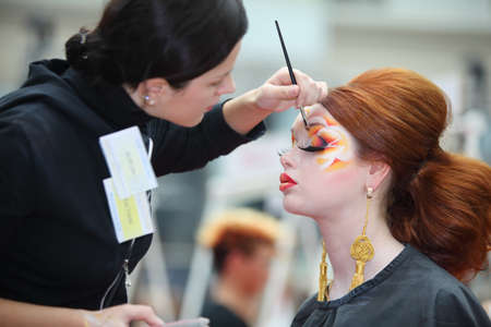 visagiste: MOSCOW - OCTOBER 2: Visagiste makes original makeup for redheaded model at XVII International Festival World of Beauty - 2010 in exhibition complex Gostiny Dvor, on October 2, 2010 in Moscow, Russia.