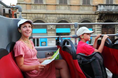 young mother and little son looking on street of Rome in tour bus in Rome, Italy, focus on mother photo