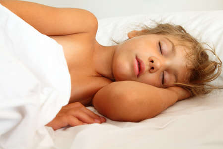 bedstead: beautiful little girl asleep in bed on white sheet and pillow