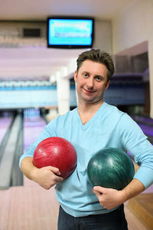 governed: Man stands in club and holds two balls for bowling