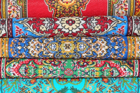 varicoloured: Seven varicoloured carpets lie in rouleau on each other on horizontal line