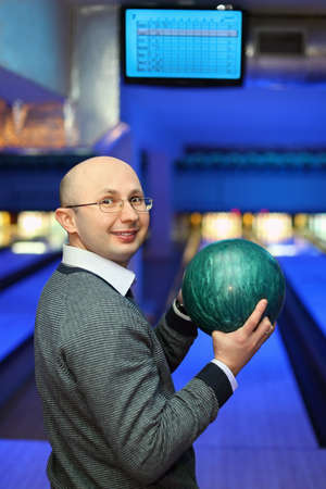 tabulation: Man in glasses stands sideways and holds  ball for bowling