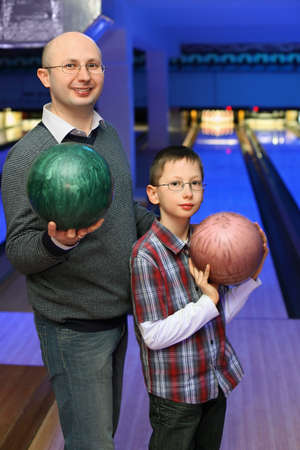 governed: Father and son in glasses stands sideways and holds  balls for bowling Stock Photo