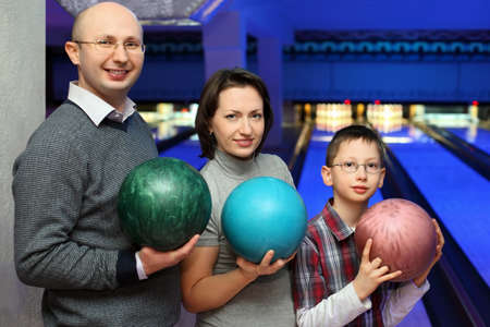 governed: Mother, father and son, stand alongside and hold balls for bowling, focus on son