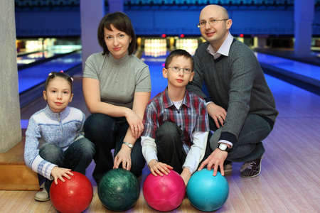 Family from four persons  of squatting in club for bowling and holds on to balls, focus on children and balls photo