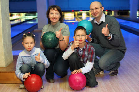 show off: Family of squatting in bowling club and shows  hands of ok, focus on children