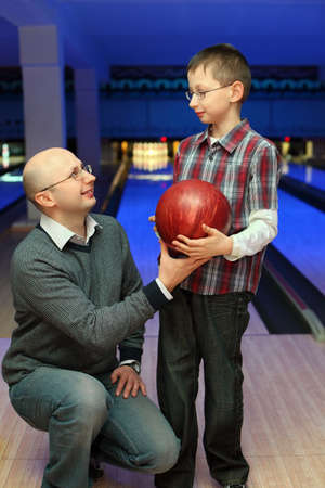 gives: Father gives  son  red ball for bowling