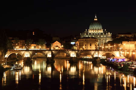 Sant' Angelo Bridge and Basilica of St. Peter at night in Rome, Italy photo