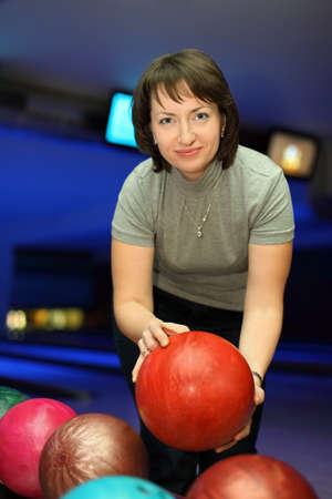 tabulation: Woman takes  ball for playing in bowling and smiles Stock Photo