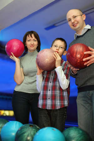 Mother, father and son, stand alongside and hold balls for bowling, focus on father and son photo