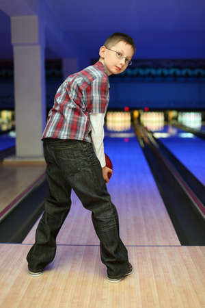 qualify: Boy looks back and qualify to throw  ball for bowling