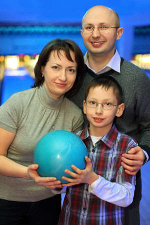 Mother, father and son, stand alongside and hold one ball for bowling photo