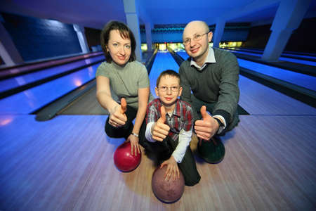 Family of squatting in bowling club and shows  hands of ok, focus on  boy photo