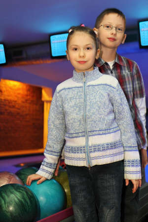 Brother and sister stand alongside near balls for bowling, focus on girl photo