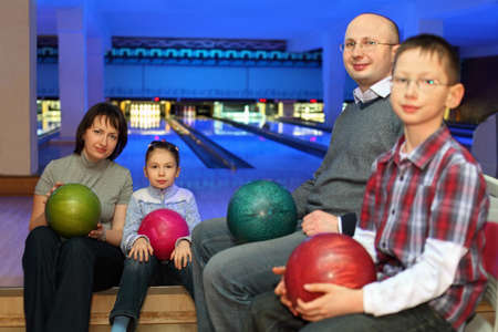 Mother, father and two children, sit in club and hold balls for bowling on knees, focus on  girl and mother photo