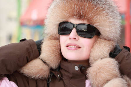 beautiful young woman in fur hat and sunglasses in winter, childrens playground photo