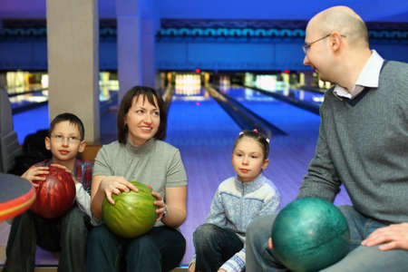 Four persons sit communicate in bowling club and hold balls, focus on mother and daughter