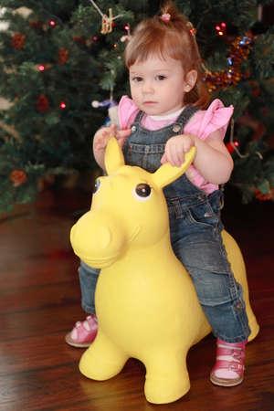 ass christmas: beautiful little girl sitting on yellow toy donkey, Christmas tree Stock Photo
