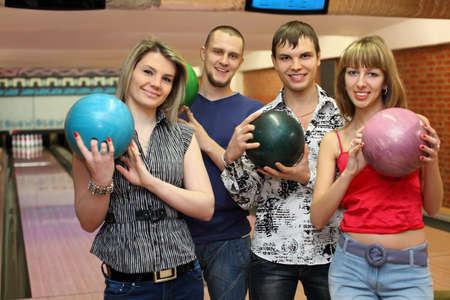 young fellow: Two fellows and two girls stand in club and hold balls for bowling, focus on fellow on left