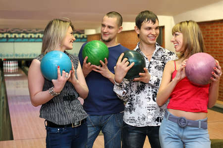 Two in lovers couple stand with balls for bowling and look on each other, focus on  fellow on left photo