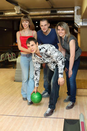 fellow: Man prepares throw  ball in bowling club and friends him encourage , focus on fellow in center Stock Photo