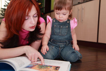 beautiful young mother and her little daughter in denim jumpsuit reads book photo
