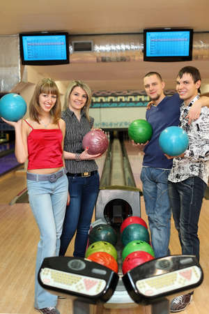 governed: Four students stand near tenpin bowling with balls for playing bowling and smile, focus on girl in center Stock Photo