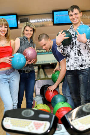 governed: Two girls and two youths stand near tenpin bowling with balls for playing bowling and smile, focus on girl and fellow on sides