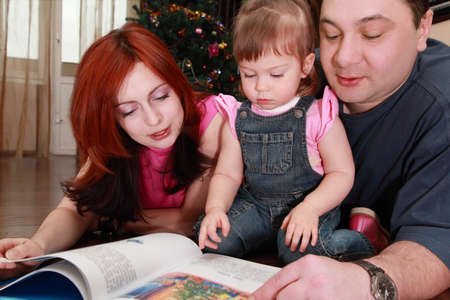 jumpsuit: mother, father and little daughter in denim jumpsuit reads book, Christmas tree, focus on girl