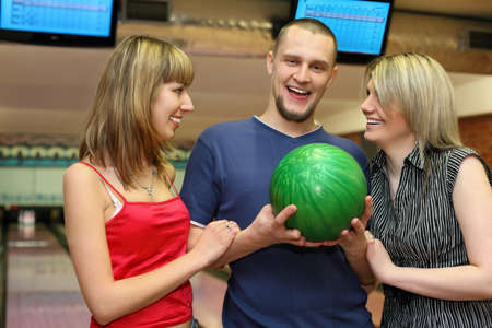 Two girls and man stand alongside and laugh merrily, focus on man photo