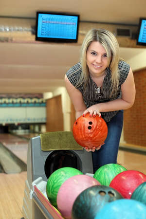 governed: Girl takes two hands ball for playing bowling Stock Photo