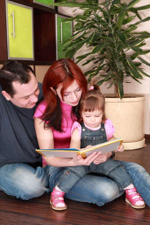 jumpsuit: mother, father and little daughter in denim jumpsuit reads book on floor