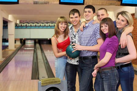 fellow: One fellow holds ball for bowling and his friends stand alongside with him and smile, focus on  fellow in center and on girls on right