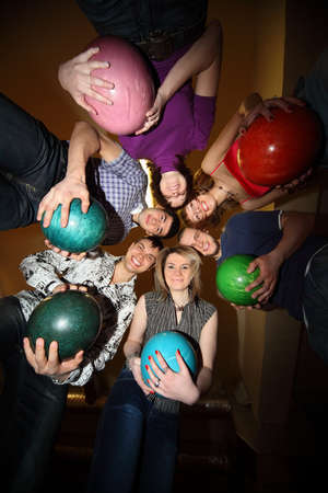 gets: Girls and youths stand in close circle and everybody gets on  hip  ball for bowling Stock Photo