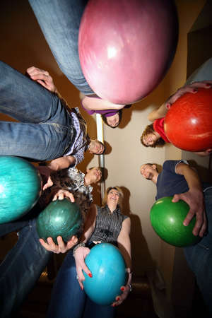Girls and youths stand in circle and everybody hold ball for bowling and laughs photo