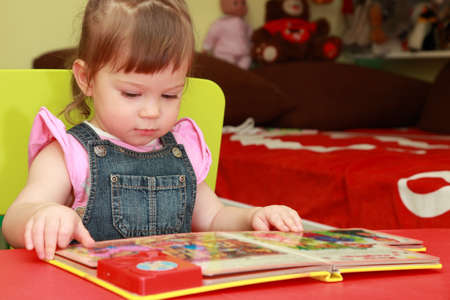 beautiful little girl in denim jumpsuit and pink shirt seats on yellow chair and reads book Standard-Bild