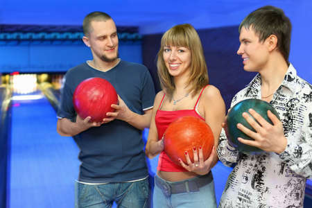 governed: Two men holds  balls for bowling and look at girl in center, focus on youth on left and girl in center