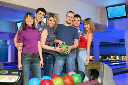 governed: Six friends stand near stand ruling balls and going to play in bowling