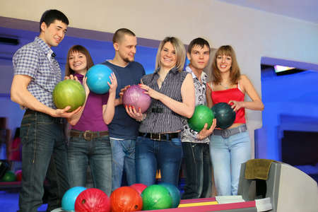 everybody: Six friends stand near stand ruling balls and everybody holds  ball for bowling Stock Photo