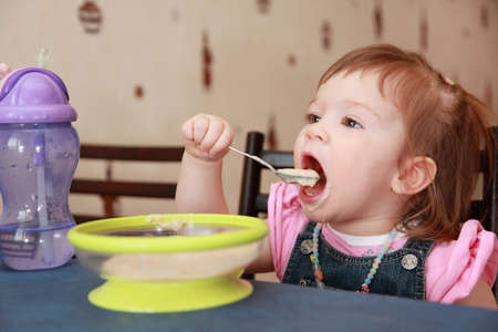 beautiful little girl in pink shirt eating porridge, bedraggled face Stock Photo - 17730334