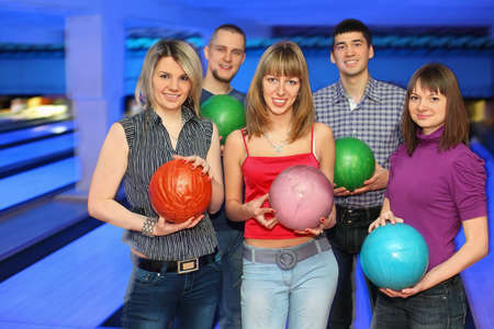 governed: Three girls and two men stand alongside and everybody holds  ball for bowling, focus on girls