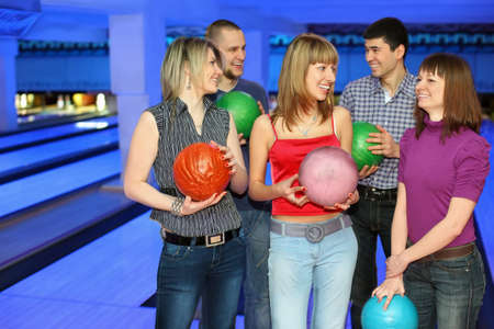 Five friends stand with balls for bowling and look on each other, focus on girl in center and on right photo