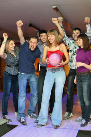 exactness: Woman prepares for throw  ball in bowling and friends it encourage, focus on girl in center