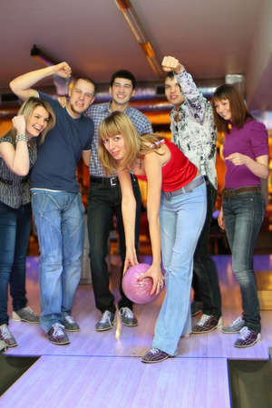 exactness: Girl prepares throw  ball in bowling club and friends it encourage scream and gestures, focus on girl in center Stock Photo