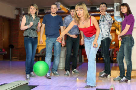 exactness: Girl throw ball on lane for bowling and friends worry for result, focus on girl in center