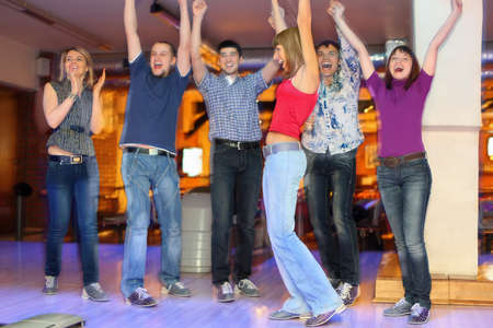 Friends are glad and lift hands upwards for successful throw of girl in center photo
