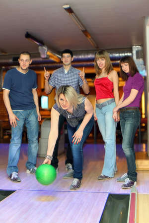 exactness: Girl prepares for throw  ball in bowling and friends hearten it, focus on girl in center Stock Photo
