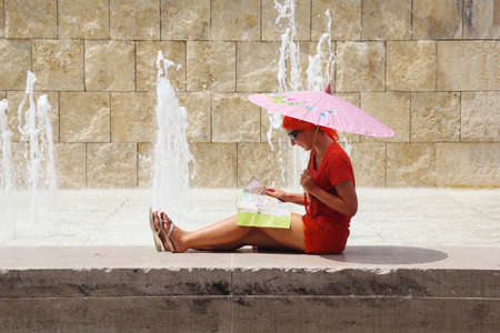 beautiful young woman sitting near fountain and looking at map, Rome, Italy Stock Photo - 17719165